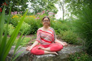 Jennifer sitting in a park ready to meditate